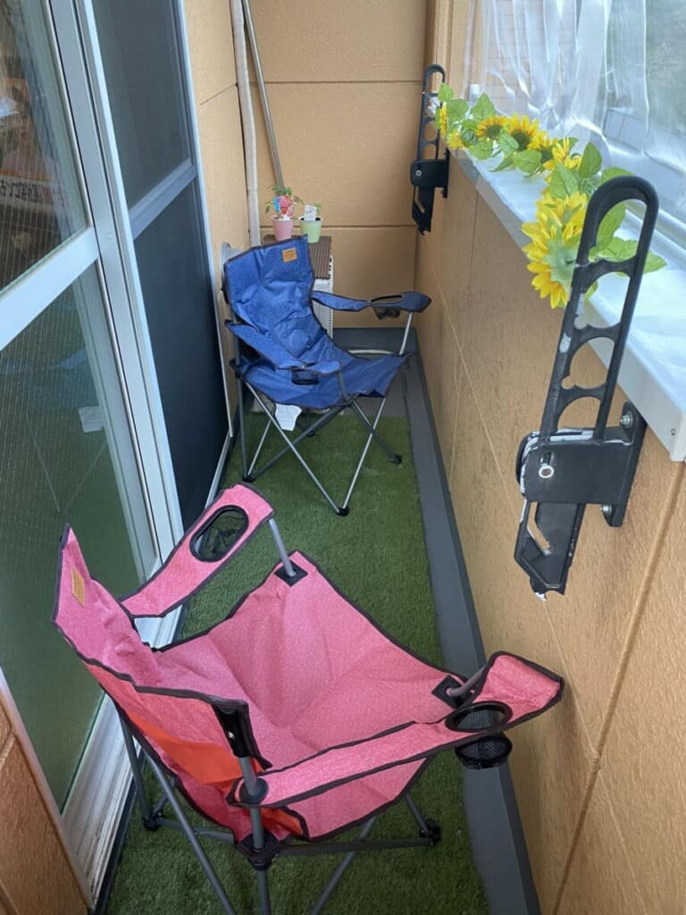 Two camp chairs and fake grass on balcony