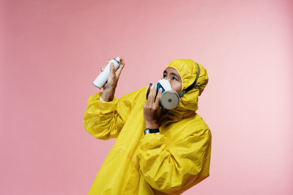 Person in coveralls holding spray bottle.