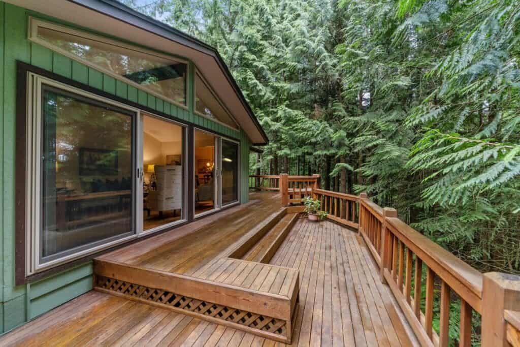 Large wood deck attached to forest home.